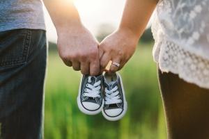 Paar hält Kinderschuhe in der Hand