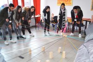 Teamarbeit: Teilnehmende der Programme versuchen gemeinsam Holzklötze aufeinanderzustapeln.