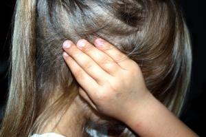 Ein Mädchen hält sich die Ohren zu