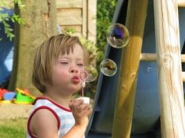 Ein behindertes Mädchen pustet Seifenblasen