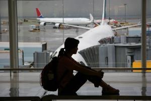 Eine Frau mit Rucksack sitzt im Flughafen vor einem Fenster