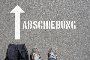 """Füße vor dem Schriftzug """"Abschiebung"""" auf dem Boden (Foto: Shutterstock)"""