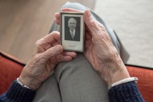 Eine alte Frau hält das Foto ihres verstorbenen Mannes in den Händen. (Foto: Pixabay)