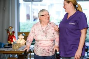 Pflegekraft mit alter Dame in ihrem weihnachtlich geschmückten Wohnzimmer