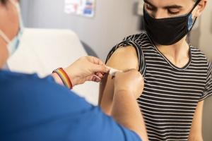 Arzt impft jungen geflüchteten Mann gegen das Corona-Virus