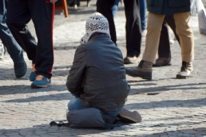 Bettler kniet auf der Straße