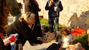 Eine ältere Frau gibt einer Flüchtlingsfamilie am Wegesrand Essen
