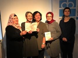 Fünf Frauen halten ein Buch hoch