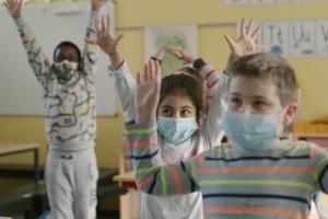 Kinder mit Masken strecken die Hände in die Höhe