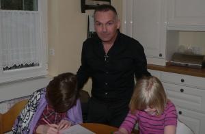 Vater Serjan steht hinter Küchentisch, an dem zwei Kinder sitzen