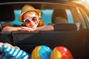 Kind mit Strohhut und Sonnebrille im Auto (Foto: Shutterstock)