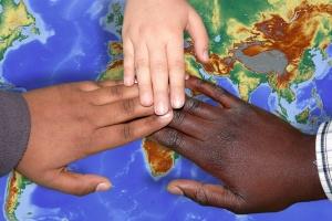 Hände unterschiedlicher Hautfarbe auf einer Weltkarte