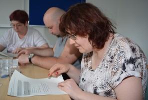 Drei Leute sitzen an einem Tisch und lesen Texte