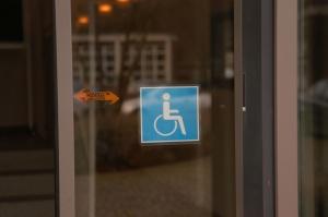 Glasschiebetür mit Logo Rollstuhl