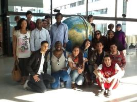 Internationale Studierende knien und stehen vor einer Weltkugel