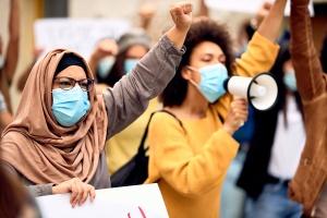 Zwei Frauen demonstrieren  während der Corona-Pandemie gegen  Rassismus.