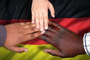 Hände verschiedener Hautfarben auf der Deutschlandfahne