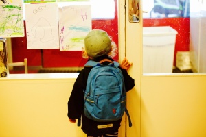 Grundschüler steht vor einem Klassenraum