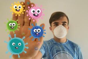 Symbolbild Junge mit Maske und Corona-Viren