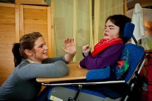 Junge  Frau kümmert sich um Frau im Rollstuhl