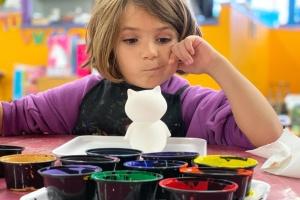 Ein Kind sitzt in der Kita vor bunten Farbtöpfen