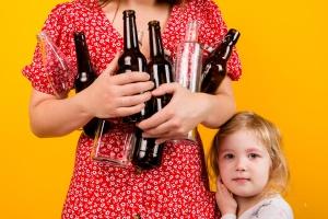 Kind mit alkoholkranker Mutter, die viele Flaschen im Arm hält (Foto: Shutterstock)