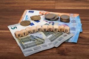 """Geldscheine und Buchstaben """"Kindergeld"""" auf einem Haufen"""