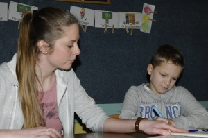 FSJlerin Kristin sitzt mit Integrationsschüler vor einem Mathebuch