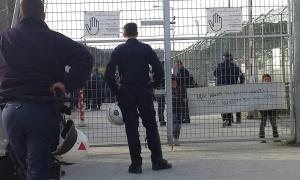 Zwei Polizisten stehen vor dem Stacheldraht des Hotspots Moria