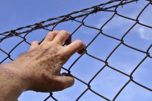 Männerhand greift in Stacheldrahtzaun