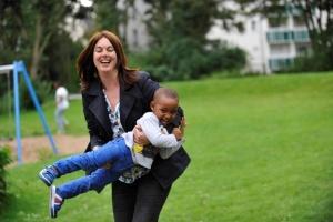 Eine Frau trägt ein farbiges Kind auf dem Arm