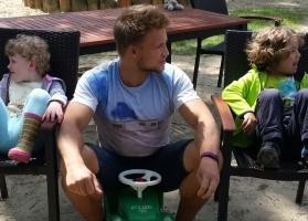 Lutz Breuckmann auf dem Bobbycar neben zwei Kindern, die auf Stühlen sitzen