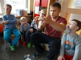 Erzieher sitzt mit Kindern im Kreis