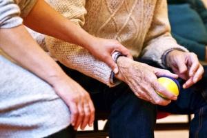 Junge Frau neben einem alten Mann mit Ball in der Hand