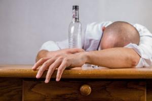 Mann mit leerer Schnapsflasche