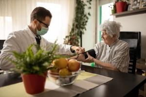 Pfleger mit Atemschutzmaske misst Blutdruck bei älterer Frau