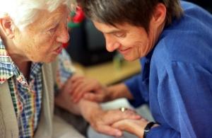 Eine Pflegerin streichelt den Arm einer alten Dame
