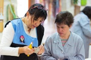 Dichtes Zusammenarbeiten wird es erst einmal nicht geben: Eine Betreuerin arbeitet eine Frau mit Behinderung an ihrem neuen Arbeitsplatz ein. (Foto: Shutterstock)