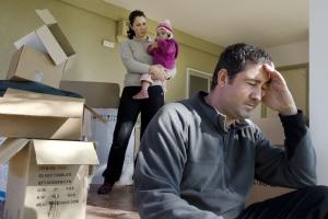 Verzweifelte Familie vor Umzugskisten (Foto: Shutterstock)