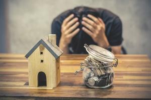 Verzweifelter Mann vor Miniaturhaus und Gelddose (Foto Shutterstock)