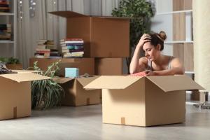 Verzweifelte Frau sitzt vor einem Umzugskarton