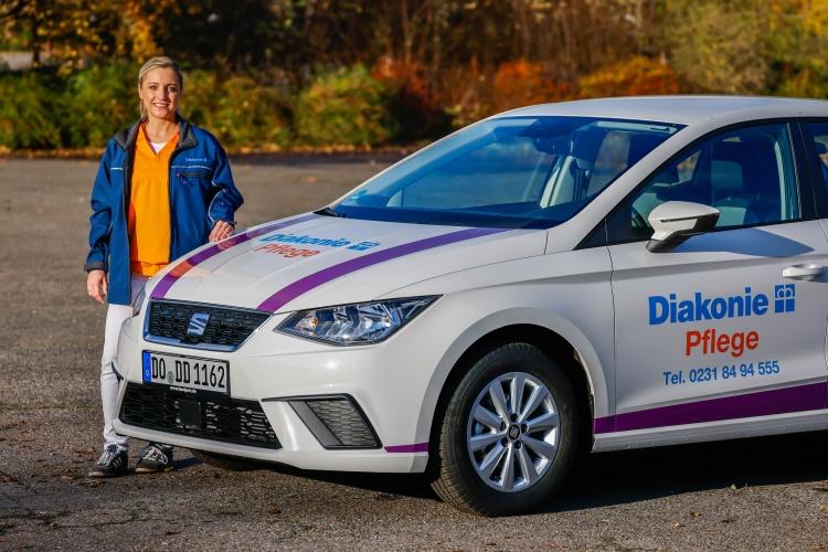 Pflegekraft der Diakonie Dortmund mit Auto (Foto: Diakonie Dortmund)