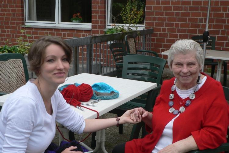 Eine Freiwillige sitzt am Tisch und hält die Hand einer älteren Dame