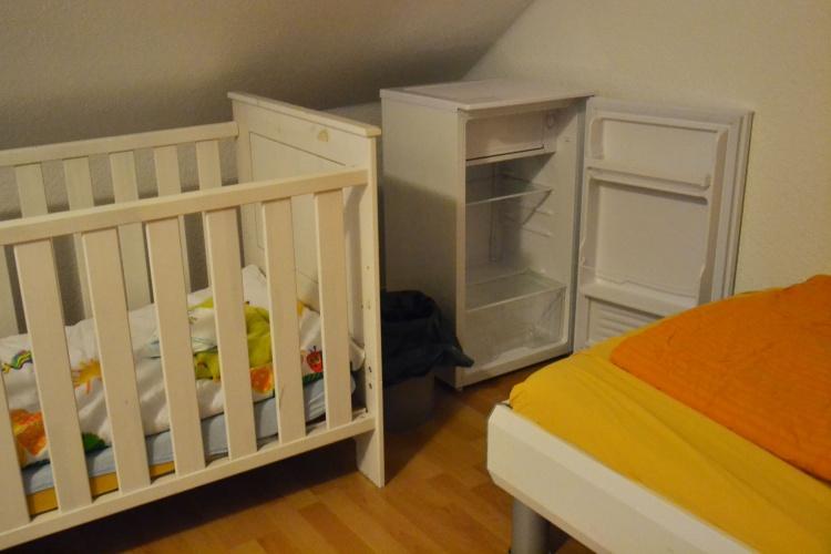Neben der Krippe steht ein kleiner Kühlschrank im Familienzimmer des Frauenhaus Herten.