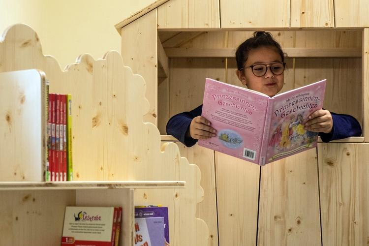 Lesen mit Ausblick: Eine Schülerin der OGS-Betreuung an der Grundschule Ruhrort schmökert in einem Buch. (Foto: Ev. Bildungswerk im Kirchenkreis Duisburg)
