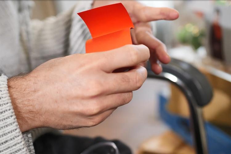 Hand, die einen roten Zettel mit einer Frage hält