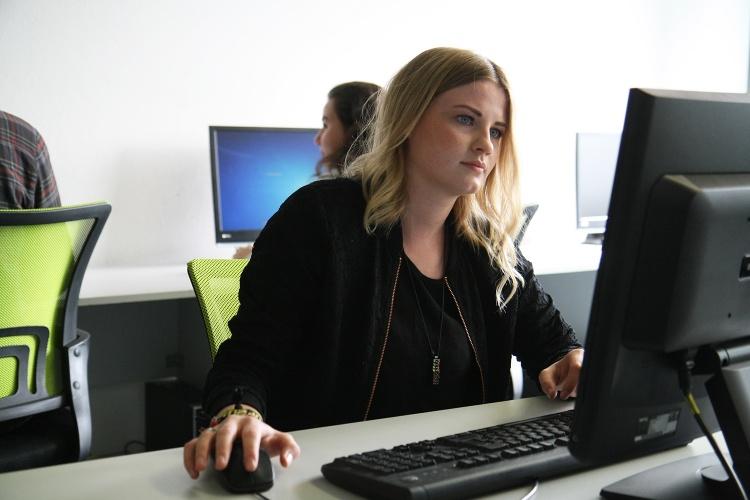 Eine junge Frau sitzt bei der low tec am Computer