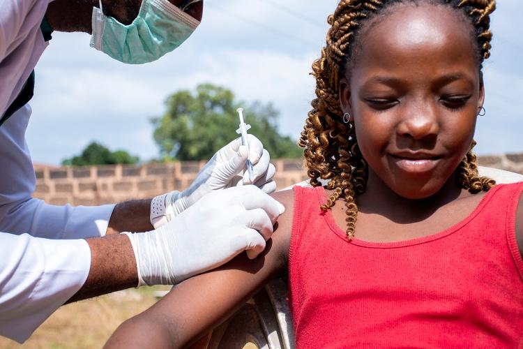 Ein afrikanischer Arzt impft ein Mädchen