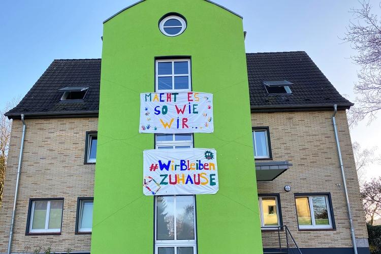 Zuhause bleiben: An der Außenfassade der Evangelischen Jugendhilfe Oberhausen prangt ein selbst gemaltes Banner. (Foto: Ev. Jugendhilfe Oberhausen)