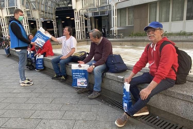 Mitarbeiter der Bahnhofsmission Düsseldorf überreicht Essenstüten an Obdachlose vor dem Bahnhof (Foto: Bahnhofsmission Düsseldorf)